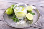 Lemonade in glass on tray on wooden background