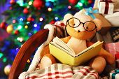 picture of teddy  - Teddy bear with book and gift boxes in rocking chair on Christmas tree background - JPG