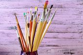 Paint brushes with paints on wooden background