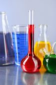 Different laboratory glassware with colorful liquid on color background
