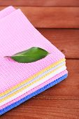 Colorful napkins with green leaf on wooden table