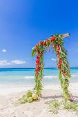 beautiful wedding arch decorated with palm trees and flowers on tropical sand beach, beach wedding setup