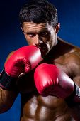 Strong Athletic Man With Boxing Gloves On A Blue Background