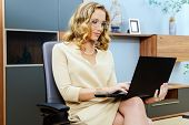 Beautiful business woman sitting on a chair and working on her laptop.