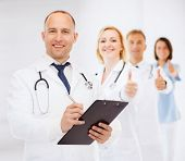 medicine, profession, teamwork and healthcare concept - smiling male doctor with clipboard and stethoscope writing prescription over white background