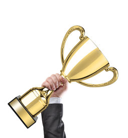 stock photo of trophy  - Businessman holding a golden cup trophy - JPG