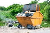 pic of dumpster  - yellow dumpster with household garbage on the roadside - JPG