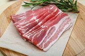 foto of bacon  - Sliced bacon with rosemary on the wood background - JPG