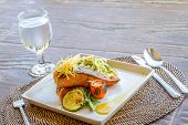 pic of salmon steak  - grilled salmon steak served with pasta and vegetables in a small outdoor restaurant - JPG