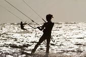image of kites  - silhouette of female kite surfer in water - JPG