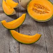 foto of muskmelon  - Fresh melons on old wooden background - JPG