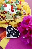 stock photo of nachos  - Happy Cinco de Mayo party table with nachos food platter and bright orange red and pink napkins on a red wood background.