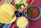 picture of tacos  - Happy Cinco de Mayo bright colorful party with ingredients for assembling tacos on festive red wood table - JPG