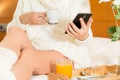 pic of wench  - Woman eating breakfast in bed while looking at your mobile phone - JPG