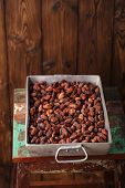 foto of cocoa beans  - roasted cocoa chocolate beans in Vintage heavy cast aluminum roasting pan on wood background - JPG