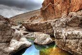 stock photo of oman  - Colorful rocks in a tranquil rock pool in Wadi Bani Khalid near Muscat - JPG