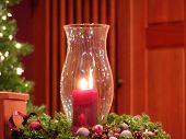 red Candle in glass chimney with christmas decorations