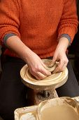 picture of molding clay  - Female hands forming clay pot on the pottery wheel - JPG