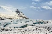 stock photo of fracture  - Storm clouds gathering over the fractured blue ice of the Sv - JPG