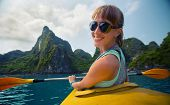 image of kayak  - Smiling lady sitting in the kayak with limestone mountains of the Ha Long Bay  - JPG