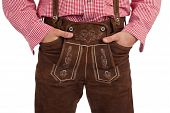 Closeup of a Bavarian man with hands in oktoberfest leather trousers (lederhose) pocket.