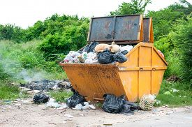 foto of dumpster  - yellow dumpster with household garbage on the roadside - JPG