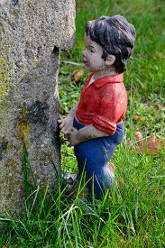 stock photo of gnome  - Little boy garden gnome standing next to a tree - JPG