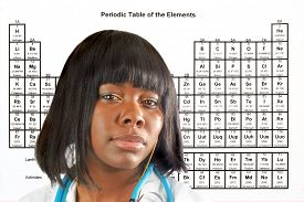 stock photo of periodic table elements  - Female doctor or scientist in front of a periodic table of elements - JPG