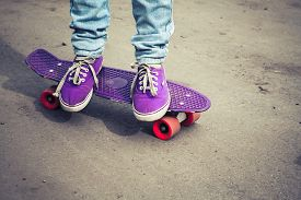 pic of snickers  - Young skateboarder feet in gumshoes and jeans standing on his skate - JPG
