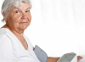 picture of manometer  - Elder woman measuring blood pressure with automatic manometer at home - JPG