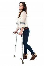 picture of crutch  - Full length image of teen walking with crutches - JPG