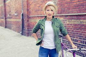 stock photo of commutator  - Hipster cyclist young beautiful girl with vintage road bike on city street urban scene - JPG
