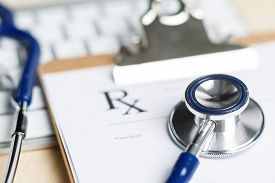 stock photo of stethoscope  - Prescription form clipped to pad lying on table with keyboard and stethoscope - JPG