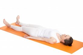 stock photo of corpses  - Sporty beautiful young woman in white sportswear lying with closed eyes on orange mat in Shavasana  - JPG