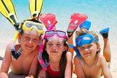 image of swimming pool family  - Three smiling children posing on a beach wearing snorkeling equipment - JPG