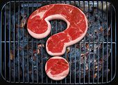 Raw meat in the shape of a question mark, grilling on the barbecue