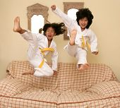 stock photo of judo  - Two little asian judo dressed girls jumping over the sofa at home - JPG