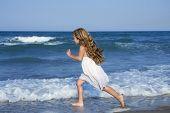 Little girl running beach shore splashing water in blue sea