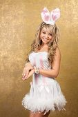 sexy blonde woman in white dress and ears on golden background