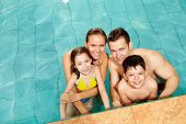 foto of swimming pool family  - Photo of happy family in swimming pool smiling at camera - JPG