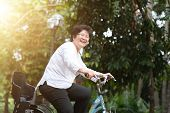 Active elderly Asian woman cycling, senior adult activity, riding bike outdoor in morning. poster