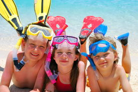 pic of summer beach  - Three smiling children posing on a beach wearing snorkeling equipment - JPG