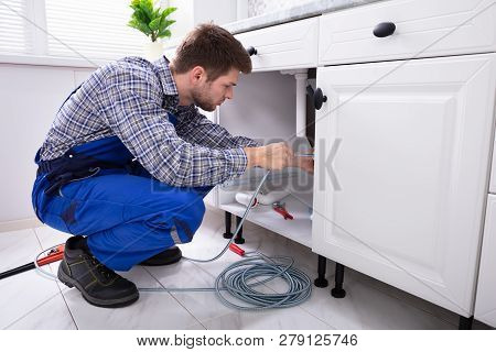 Young Male Plumber Cleaning Clogged