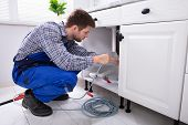 Young Male Plumber Cleaning Clogged Sink Pipe In Kitchen poster