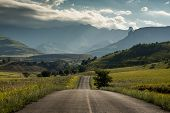 A Road Leading Towards The Royal Natal National Park And The Amphitheatre Mountain At Golden Hour, D poster
