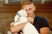 He Is More Than Just A Pet. Happy Cat Owner With Muscular Look. Cat Relaxes In Arms Of His Owner. Ha poster