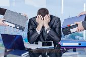 A Businessman Is Sitting At His Working Place In The Office Closing His Face With Hands In Working S poster