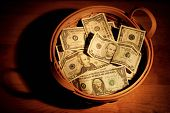 stock photo of tithe  - A basket full of money with very dramatic lighting - JPG