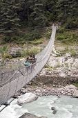 Porters Crossing A Suspension Bridge - Nepal