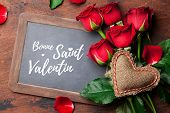 Valentines day greeting card with red rose flowers bouquet on wooden background. Bonne Saint Valent poster